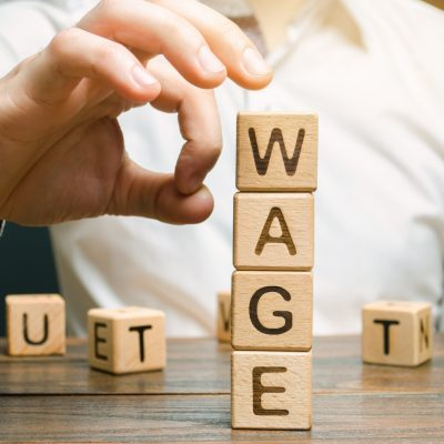 Hand of a businessman removes wooden blocks with the word Wage